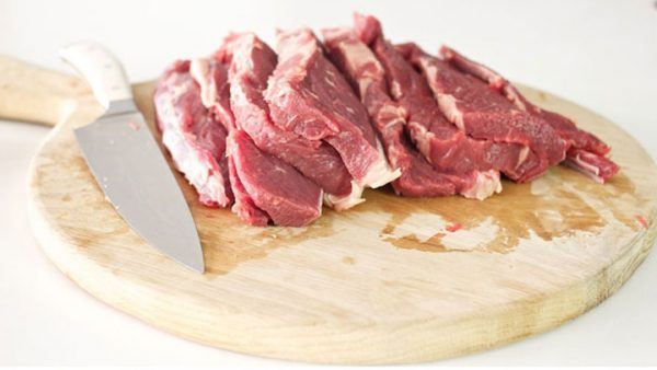 Topside beef cut into strips on a wooden board