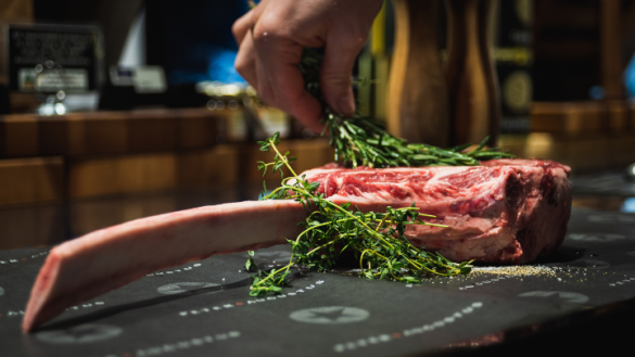 bone in rib eye steak with a close up of a hand holding rosemary
