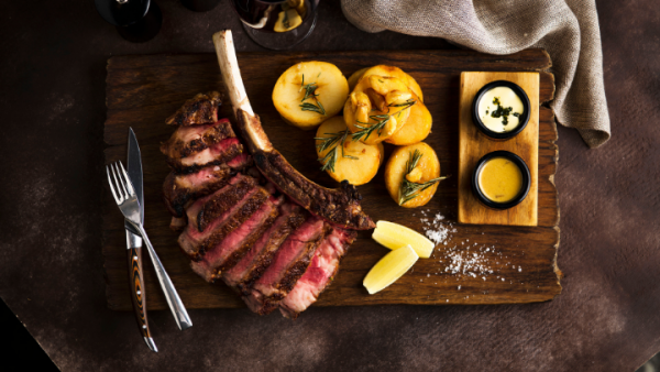 sliced tomahawk steak on wooden board with roasted potatoes and sauces from black hide steakhouse