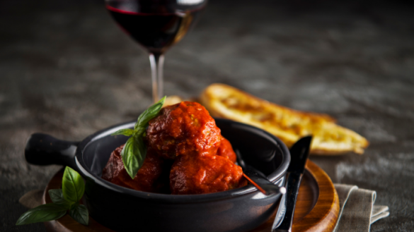 three italian meatballs in napoli sauce topped with basil in a dark bowl with glass of red wine in the background